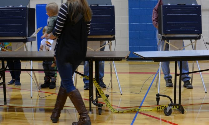 People waiting in line to vote in voting booths during an election.
